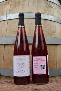 Photograph of The Book Club Wine rosé wine's front and back set against a wood wine barrel ringed with metal bands