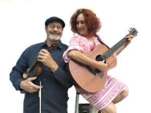 The Jamesons Duo band photo - Paul Kiteck, left, holding fiddle. Sharon Glassman with guitar, right, sitting on ladder.