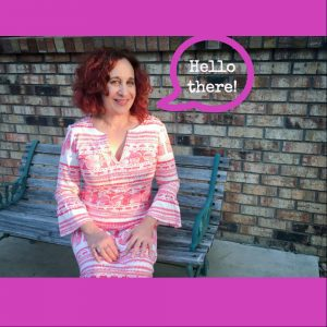 Me in pink and white Lily Pulitzer 70s dress sitting on grey wood and oxidized green wrought iron bench by brown and grey brick wall. Pink speech balloon with white type that says Hello there! Fuchsia stripes above and below photo to form a square image